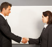 Businessman and woman shaking hands in office, smiling Stock Photos