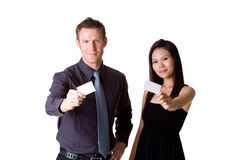 Businessman and woman showing blank  bussiness car. Businessman in formal suit and woman in dress showing business card Royalty Free Stock Photography