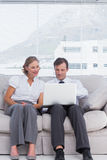 Businessman and woman sitting on couch Royalty Free Stock Images