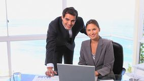Businessman and woman smiling at the camera. Which then rises stock video footage
