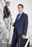 Businessman and woman in stairway Stock Photo