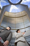 Businessman and woman standing below skylight in airport, woman using mobile phone, low angle view Stock Photos