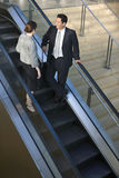 Businessman and woman standing on escalator in airport terminal, talking, elevated view Royalty Free Stock Images
