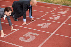 Businessman and woman on start line of running track Royalty Free Stock Photo