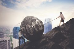 Businessman and woman with stone on hill stock images