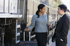 Businessman and woman talking on railway platform beside stationary passenger train, smiling, side view Royalty Free Stock Photography