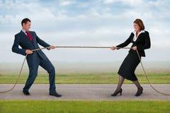 Businessman and woman tug of war. Businessman and businesswoman tug of war contest of strength Royalty Free Stock Image