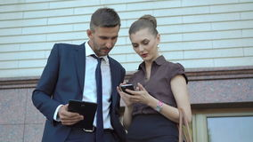 Businessman and woman using digital tablet and mobile phone near office. 4K.  stock video footage