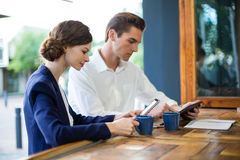 Businessman and woman using mobile phone and digital tablet at counter Royalty Free Stock Image