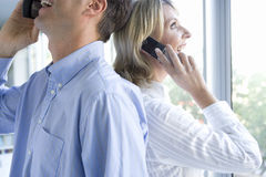 Businessman and woman using mobile phones standing back to back, smiling, side view. Businessman and women using mobile phones standing back to back, smiling stock images