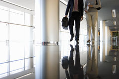 Businessman and woman walking in corridor, low section Stock Photography