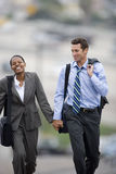 Businessman and woman walking outdoors, holding hands Royalty Free Stock Photo