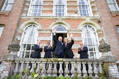 Businessman and woman waving from balcony of manor house by colleagues clapping, low angle view Royalty Free Stock Images