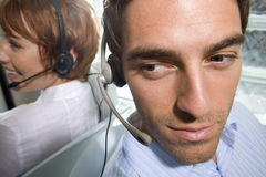 Businessman and woman wearing headsets sitting back to back, close-up, elevated view Stock Image