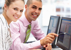 Businessman and woman working on computers Stock Photos