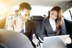 Businessman and woman working together in the car Royalty Free Stock Images