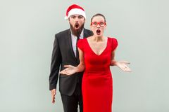 Businessman and woman looking at camera, standing together, open. Businessman and women looking at camera, standing together, open mouth with amazed face. Studio Royalty Free Stock Images