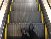 Businessman wore black leather shoes standing on the escalator. Down the elevator stock photos