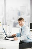 Businessman at work. Searching in personal organizer, using laptop. Looking at camera royalty free stock photo