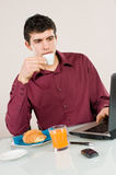 Businessman at work with breakfast Stock Photography