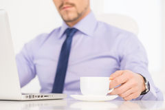 Businessman at work. Cropped image of confident young man in formalwear working at the computer and drinking coffee Royalty Free Stock Photography