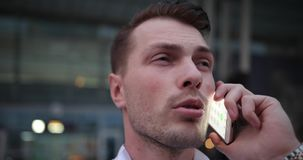 Businessman at work. Handsome young man in white shirt talks on the phone and looks around him for a taxi.  stock footage