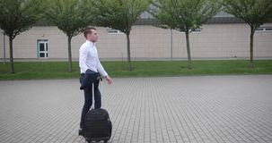 Businessman at work. Handsome young man in white shirt walks from an airport with a suitcase.  stock video footage