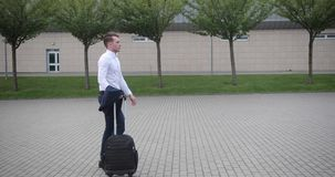 Businessman at work. Handsome young man in white shirt walks from an airport with a suitcase.  stock footage