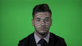 IT businessman at work with projected computer blockchain code on face blinking and thinking on green screen -. IT businessman at work with projected computer stock footage