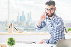 Businessman at work talking on phone. Cheerful caucasian businessman sitting at workplace and talking on cellular phone Stock Photography