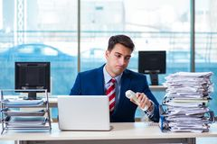 The businessman workaholic struggling with pile of paperwork. Businessman workaholic struggling with pile of paperwork Royalty Free Stock Images