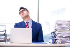 The businessman workaholic struggling with pile of paperwork. Businessman workaholic struggling with pile of paperwork Stock Photos