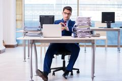 The businessman workaholic struggling with pile of paperwork. Businessman workaholic struggling with pile of paperwork Royalty Free Stock Photography