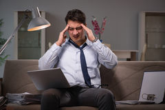 The businessman workaholic working late at home Stock Image