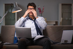 The businessman workaholic working late at home. Businessman workaholic working late at home Stock Image