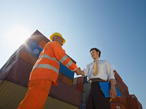 Businessman and worker with cargo containers. Mid adult businessman holding clipboard and shaking hands to manual worker near cargo containers. Horizontal shape stock photo