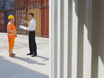 Businessman and worker with cargo containers. Mid adult businessman and manual worker standing near cargo containers. Horizontal shape, full length, copy space royalty free stock images