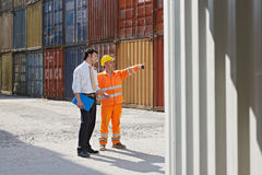 Businessman and worker with cargo containers. Mid adult businessman and manual worker standing near cargo containers. Horizontal shape, full length, copy space stock photo