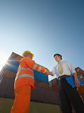Businessman and worker with cargo containers. Mid adult businessman holding clipboard and shaking hands to manual worker near cargo containers. Vertical shape stock photo
