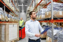 Businessman and worker on forklift at warehouse. Logistic business, shipment and people concept - businessman with clipboard and worker loading goods by forklift Stock Images