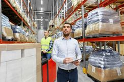 Businessman and worker on forklift at warehouse. Logistic business, shipment and people concept - businessman with clipboard and worker loading goods by forklift Stock Photography