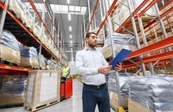 Businessman and worker on forklift at warehouse. Logistic business, shipment and people concept - businessman with clipboard and worker loading goods by forklift Royalty Free Stock Images