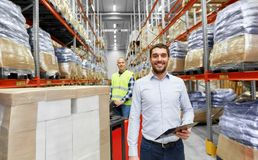Businessman and worker on forklift at warehouse. Logistic business, shipment and people concept - happy businessman with clipboard and worker loading goods by Stock Photo