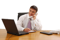Businessman Working. Businessman sitting at a table while talking on the phone and looking at his laptop Stock Photography