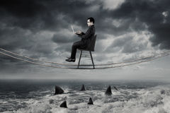 Businessman working above dangerous sea. Young businessman working with laptop computer on the rope while sitting on the chair above dangerous sharks on the sea Royalty Free Stock Photos