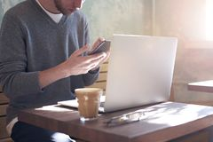 Businessman working alone on laptop and using mobile smartphone in sunny cafe, having coffee royalty free stock images