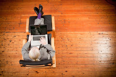 Businessman working on armchair. Businessman working on his laptop on a chair, seen from above Royalty Free Stock Images