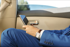Businessman working in the back-seat of a car. Young businessman sitting in the back-seat of a car, using his digital tablet Royalty Free Stock Image