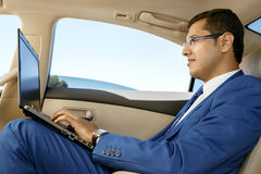 Businessman working in the back-seat of a car Royalty Free Stock Photo