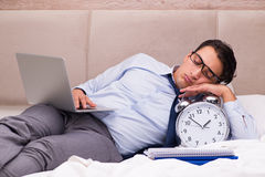 The businessman working in the bed at home Royalty Free Stock Images